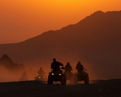 Des personnes se promènent en véhicules tout-terrain dans le désert.