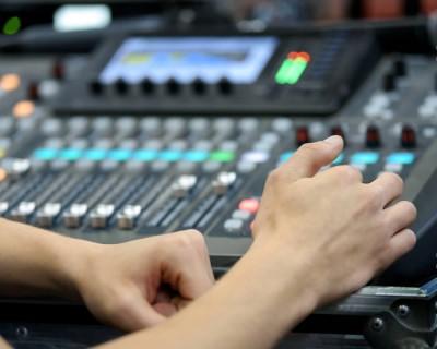 Des mains ajustent les boutons de la console de son.