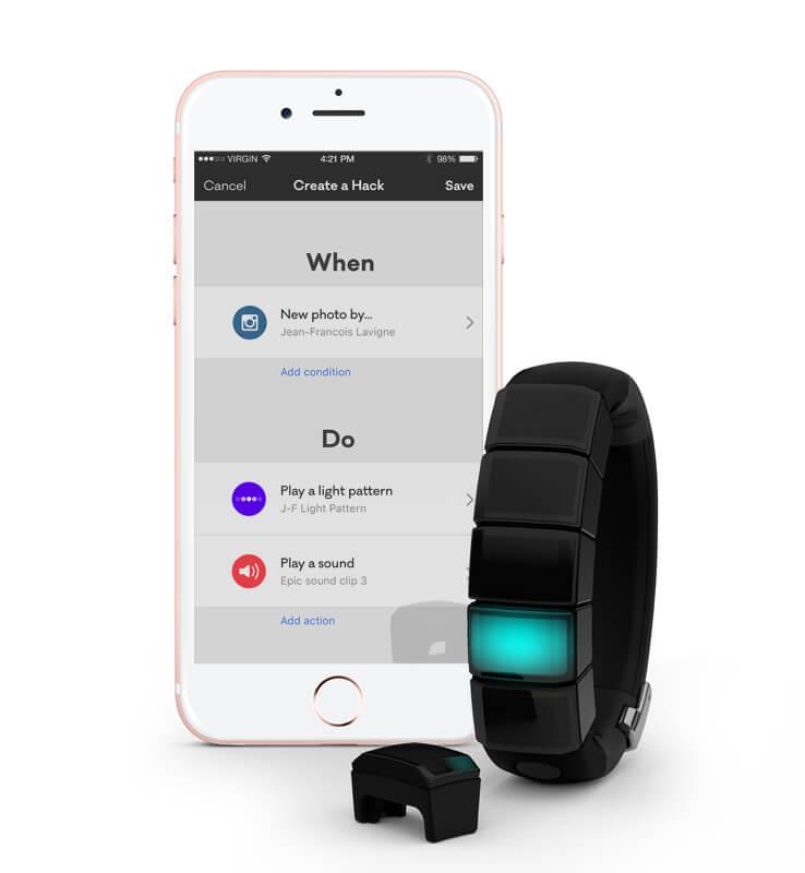 Vue 3/4 du bracelet NEX avec l'écran d'un iPhone à côté.