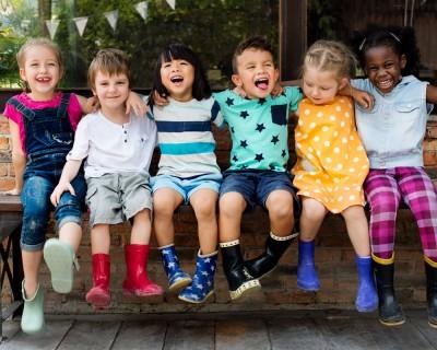 Des enfants en lignent sur un banc qui sourient.