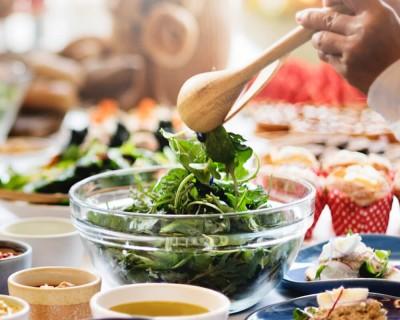Des mains touillent une salade dans un bol.