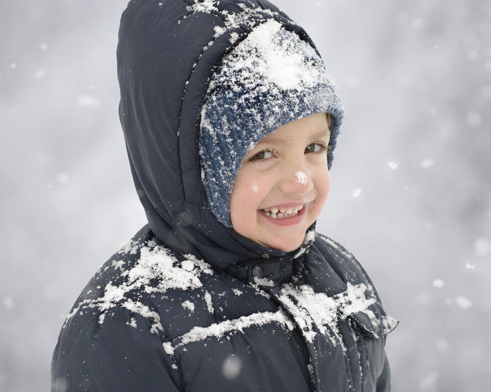 Une enfant qui sourie dans la neige.