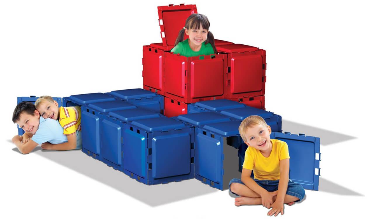 3 enfants sourient dans une structure de tunnel Brik-A-Blok.