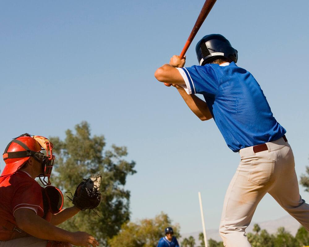 Joueur de baseball au marbre attendant un lancer pour frapper.