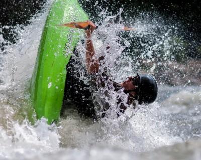 Un kayakiste fait une manoeuvre dans les rapides.