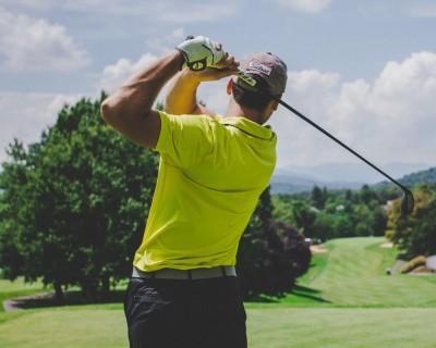 Un homme frappe une balle de golf.